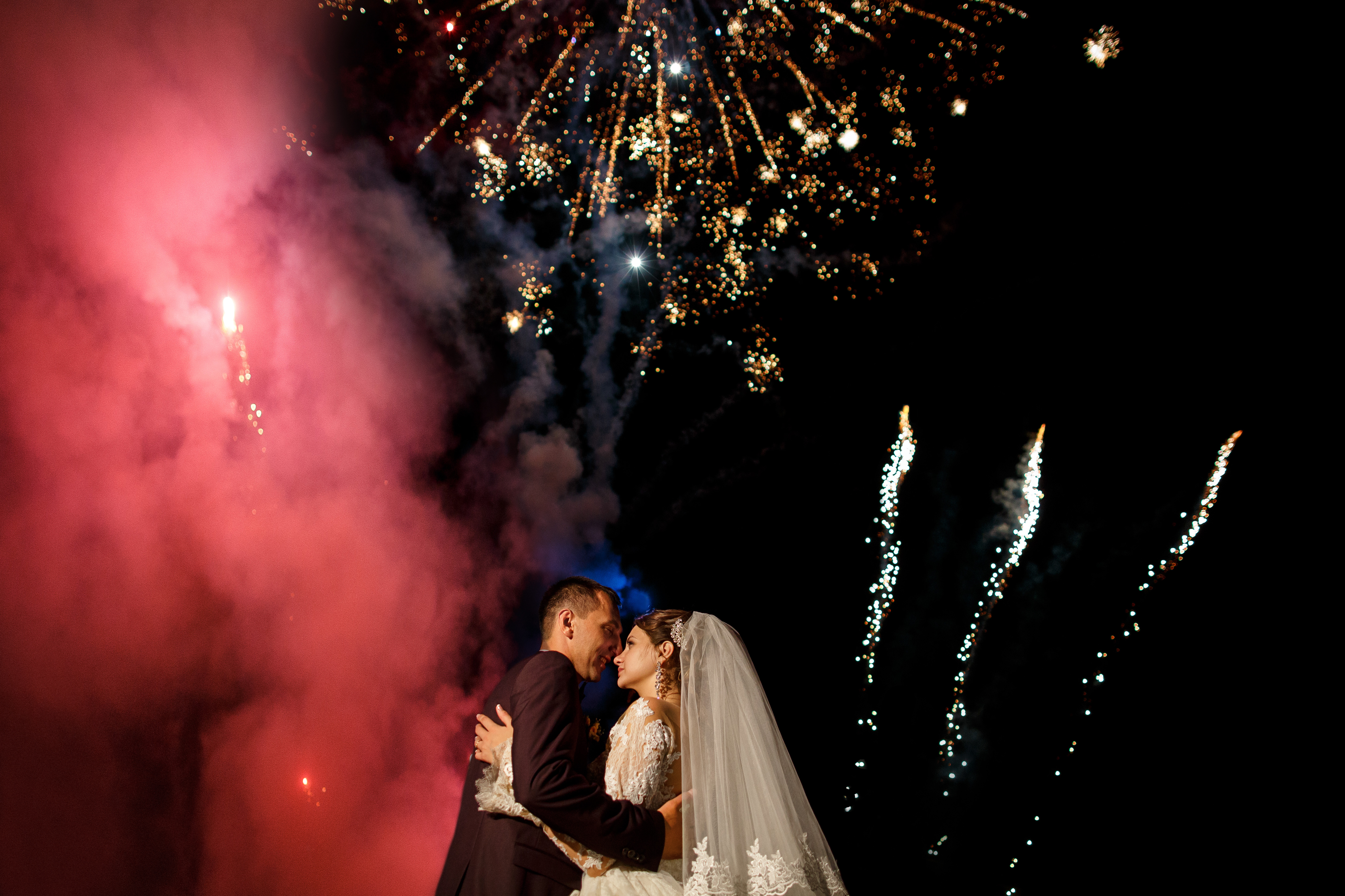 Wedding fireworks. Bride and groom hugging in the night on firework and salute background, wedding party